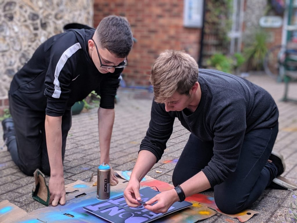 Two Young Adults do some graffiti outside of Old School House