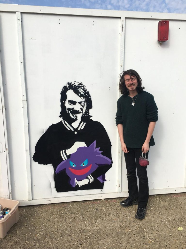 Woodie next to his artwork outside Old School House