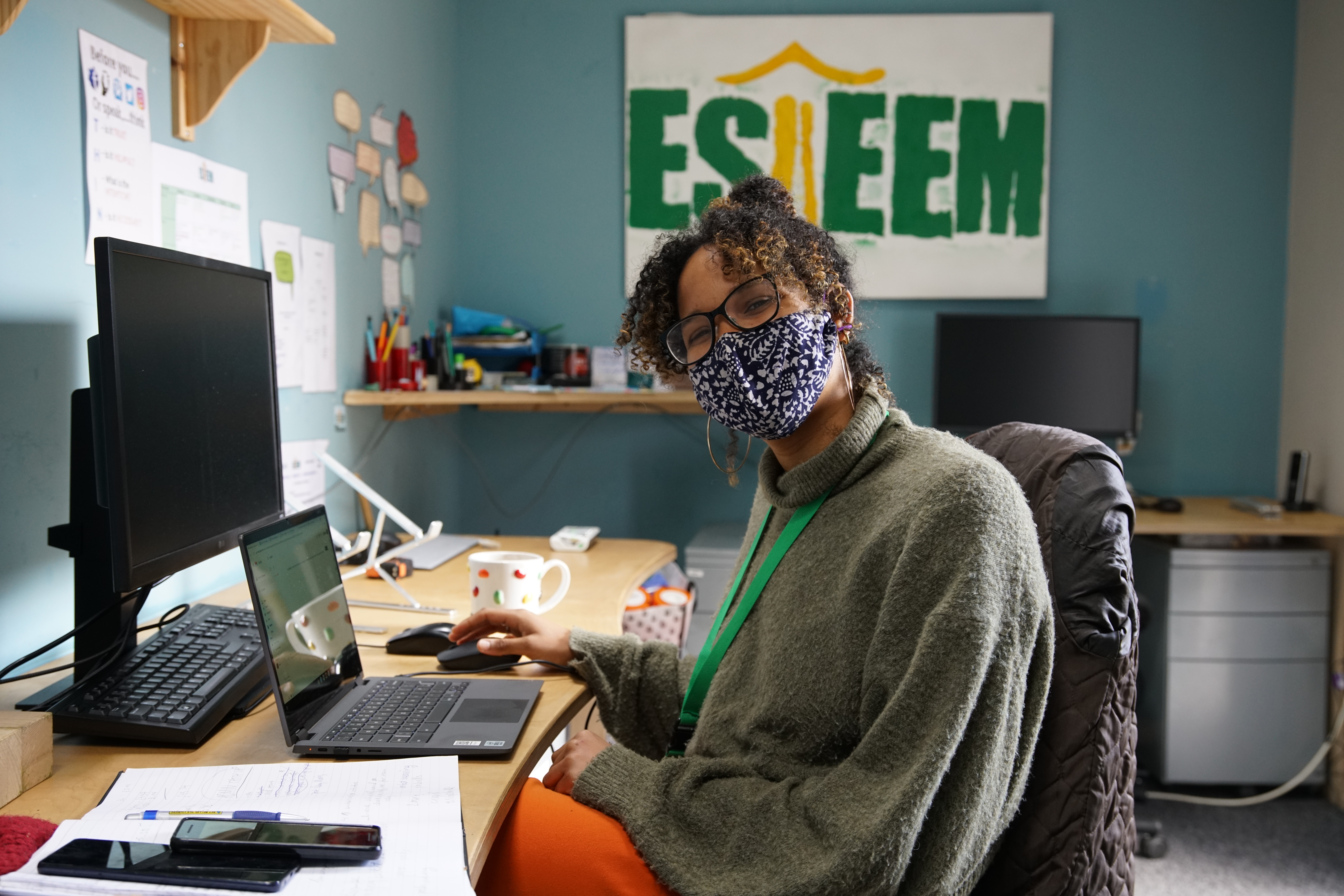 Staff Member smiling with mask on in the office